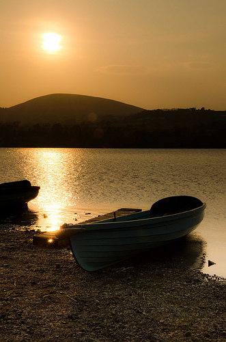 Boats moored at the edge of a lake during a golden sunset