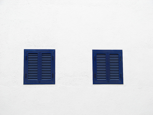 Bull shuttered windows on white wall architectural detail