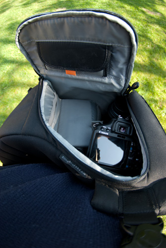 Sling bag slung round to the front with side open for easy access of camera and lenses