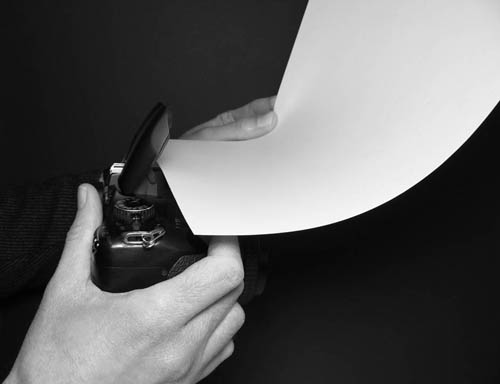 Holding a piece of card in front the camera's pop-up flash and bending it up towards the ceiling.