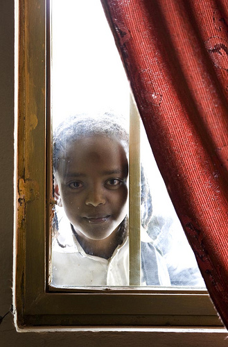 Girl framed by window and curtain
