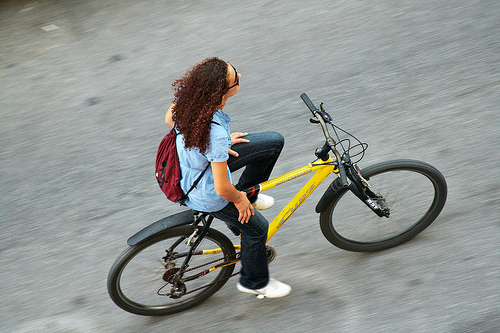 High angle panning shot of woman riding a bike