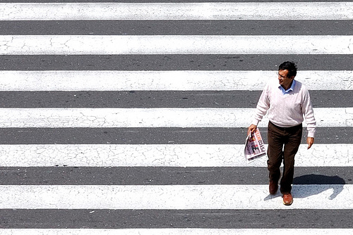 High angle photo of man crossing a pedestrian crossing