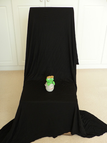 Black cloth draped over back of chair for use as seamless backdrop