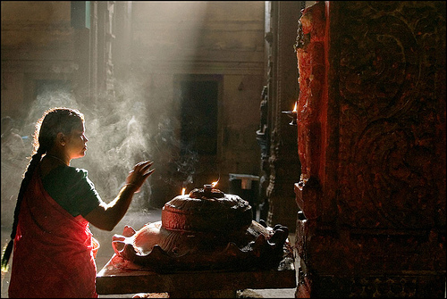 Woman praying in Meenaskshi temple, Madurai. Atmospheric lighting emphasizing smoke from incense.