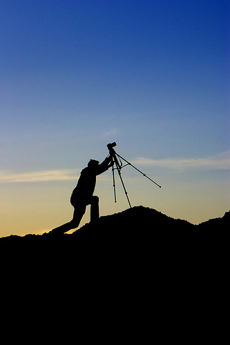Silhouette photo of a photographer positioning their tripod