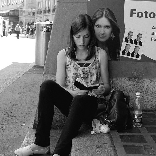 Street photo of girl reading with a poster behind looking over her shoulder, photographed using a large sensor compact camera