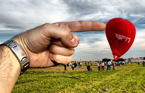 Forced perspective photo of a giant hand pushing a hot air balloon