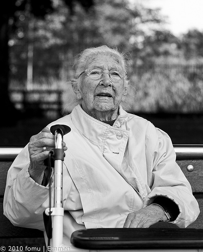 Black & white street photo of an elderly woman resting