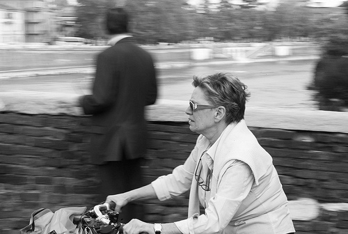 Street photo of a woman on a bike, taken using a 50mm lens