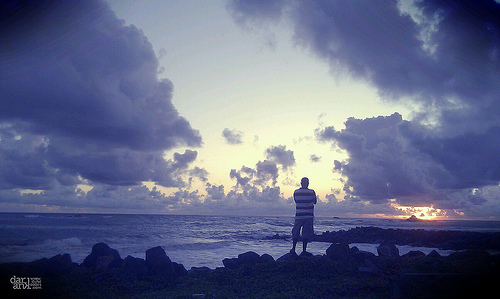 Contemplation - person standing by the ocean, captured using a camera phone