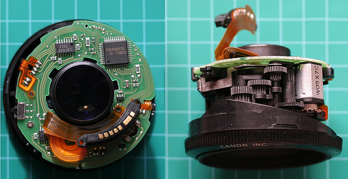 Dismantled canon lens showing electronics and autofocus motor
