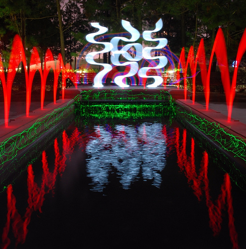 Elaborate large light painting around a pond incorporating a variety of lights