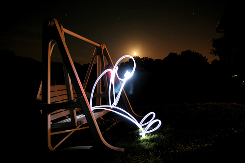 Light painting of a person sitting on a swing seat