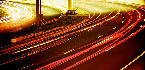 Light trails from cars entering and exiting a tunnel