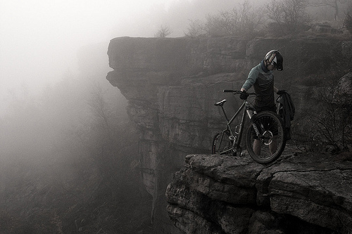 Mountain biker with negative space behind the subject, emphasizing the misty landscape