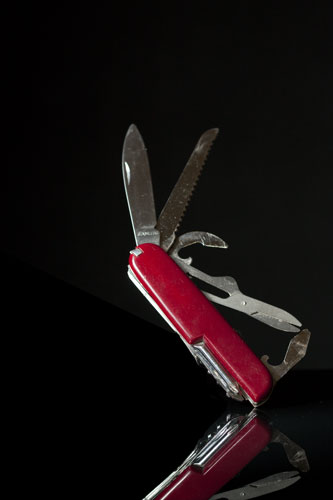 Product photo of penknife titled at an angle after painting black over the plasticine in Photoshop
