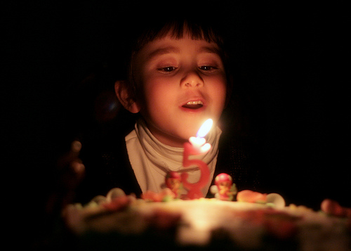Child blowing out candles on their birthday cake