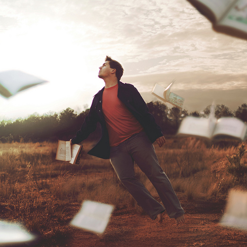Man floating in whirlwind with books flying around him