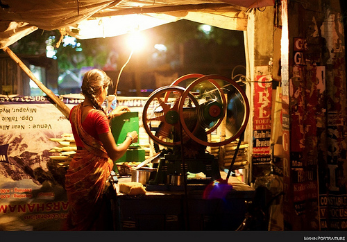 Sugarcane juice vendor in Hyderabad, India - large aperture (f/1.8) used to compensate for the low light levels