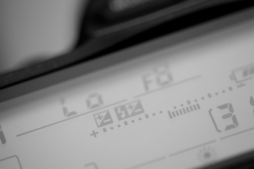 Top LCD of a Nikon camera showing the exposure meter with -1.3EV of exposure compensation applied