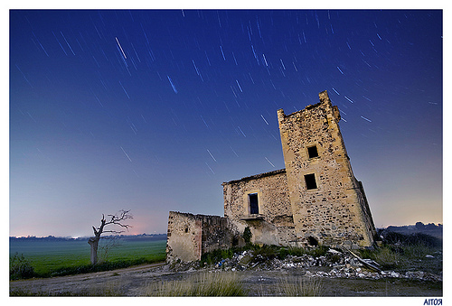 Startrails over abandoned building