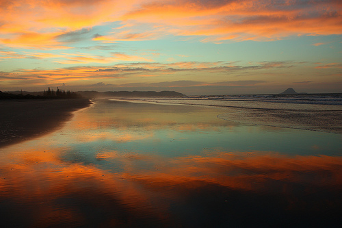 Sunset reflected in the wet sand at Ohope Beach, New Zealand