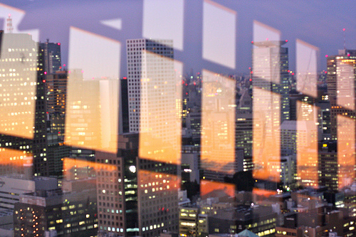 Sunset reflected in window, City skyline visible through window