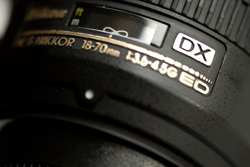 DX designation on a Nikon lens indicating it is designed for cameras with an APS-C sized sensor