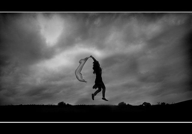 Silhouette of a person jumping while holding a transparent cloth against a backdrop of stormy clouds - purposefully breaking the rules of photography by having a centered subject, shooting against the light, and the image being heavily underexposed.