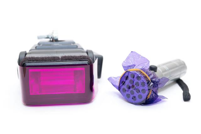 Speedlight flash with a purple flash gel attached and flashlight with a purple sweet wrapper attached
