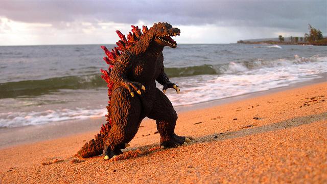 Godzilla action figure on the beach