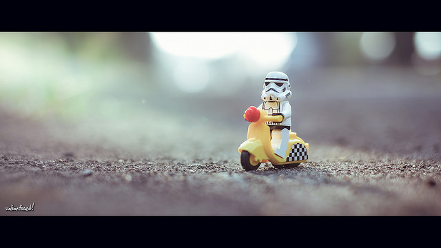 Photo of a lego Stormtrooper figure on a lego scooter riding a long a road - very thin depth of field