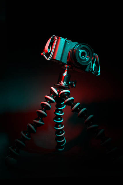 Camera on a gorillapod with multicolored lighting.