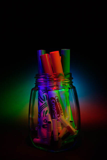 Photo of colored pens in a glass jar with multicolored lighting.