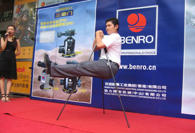 Man hanging from a tripod at a demonstration by tripod manufacturer Benro
