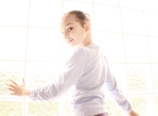 Portrait of a girl posing in front of a window, shot in manual exposure mode with exposure set to create a high key image