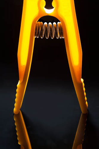 Close-up macro photo of a backlit yellow plastic clothes peg, with a black background