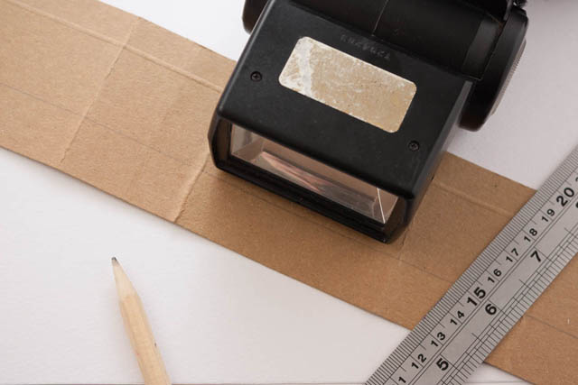 Speedlight flash on strip of cardboard with ruler and pencil for marking and bending the card