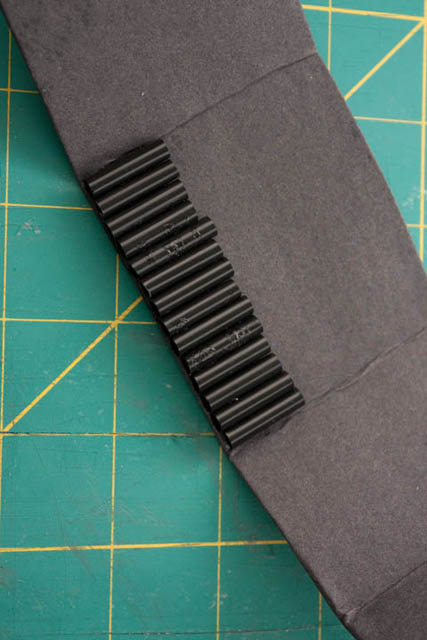 Card covered in black paper with a row of 2 cm black straw sections glued to it