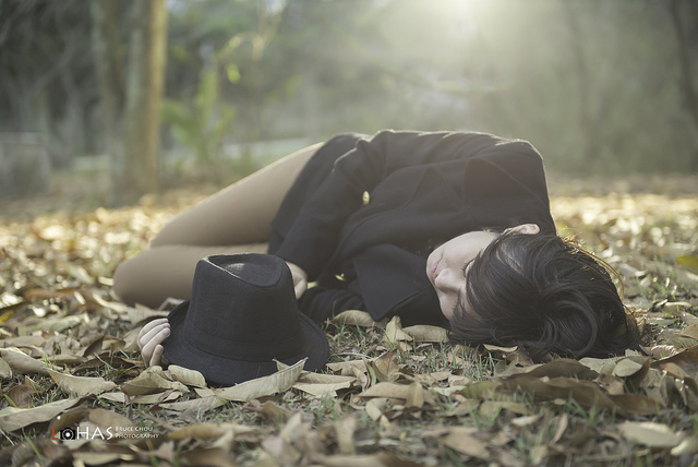 Portrait of a woman lying on the floor amongst leaves. She is backlit by the low sun, and filled with flash that has a ½ CTO gel to match the warm color temperature of the late afternoon sunlight.