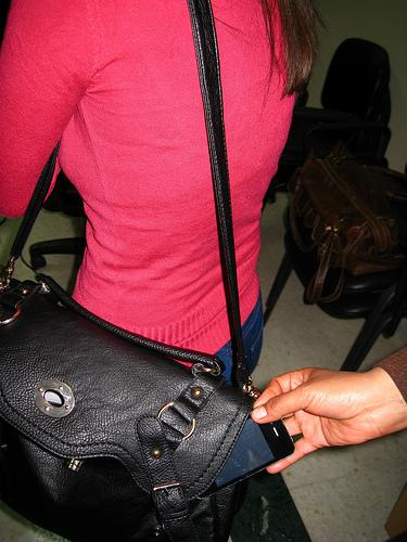Pick pocket stealing a phone from a shoulder bag / hand bag