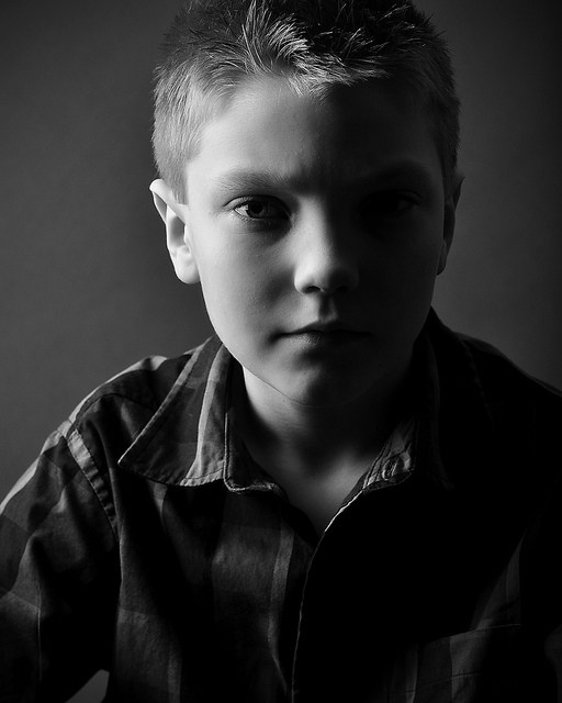 Portrait photo of a boy taken using split lighting with very little fill, so the shadow side of the subject's face appears very dark