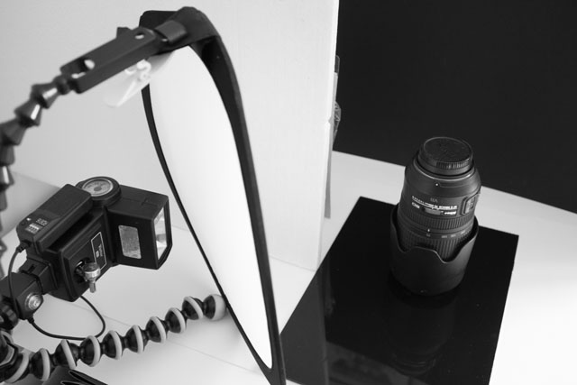 Setup for creating a low key photo of a camera lens, with a piece of polystrene used to block the light from hitting the background. (A piece of black card would have been more suitable but the polystyrene was convenient).