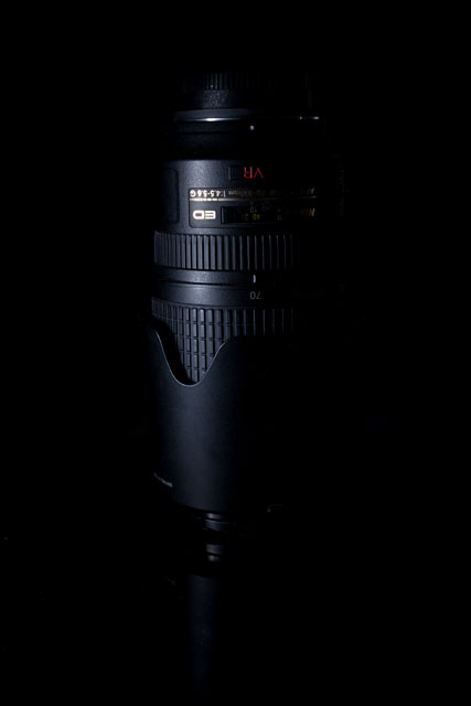 Low key photo of a camera lens, where a piece of polystrene was used to block the light from hitting the background.