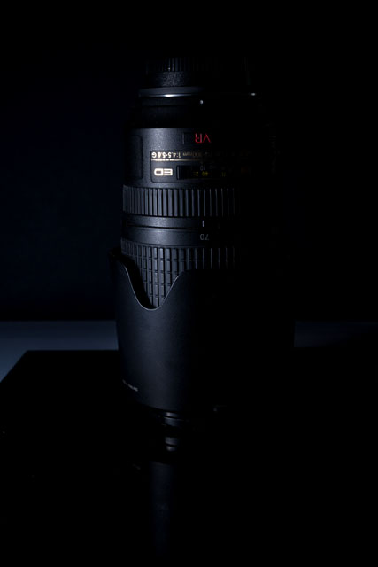 Low key photo of a camera lens, light from the flash has spilled onto the surface behind the subject a bit
