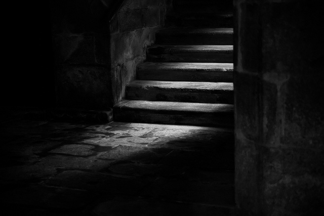 Low key photo of light highlighting steps leading down to basement