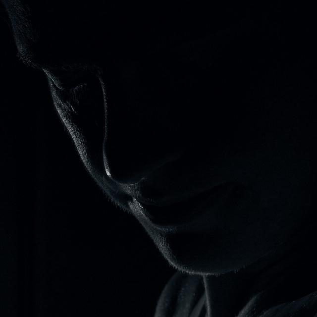 Low key portrait photo taken using a speedlight flash with a grid