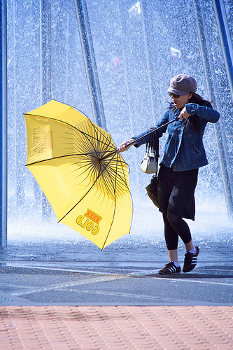 Woman With A Yellow Umbrella Against Blue Background