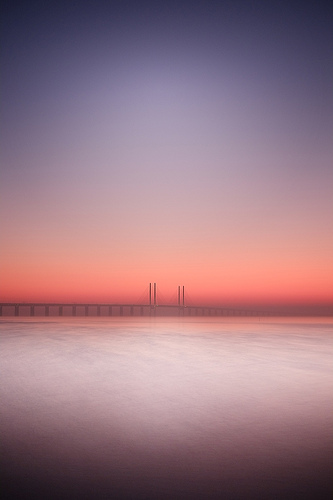 Bridge over water at sunset long exposure minimalist photograph